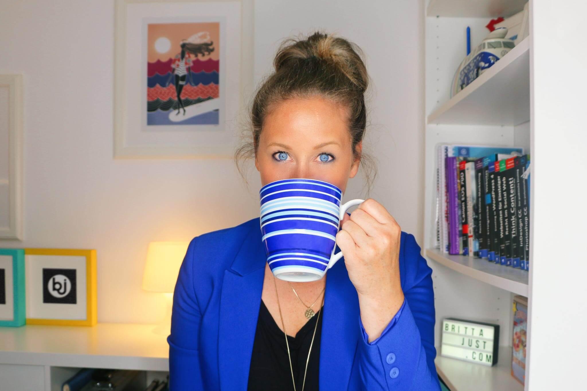 Bild von Britta im blauen Blazer, in dem sie mit ihrer blau geringelten Kaffeetasse 50 Fun Facts über sich verrät.